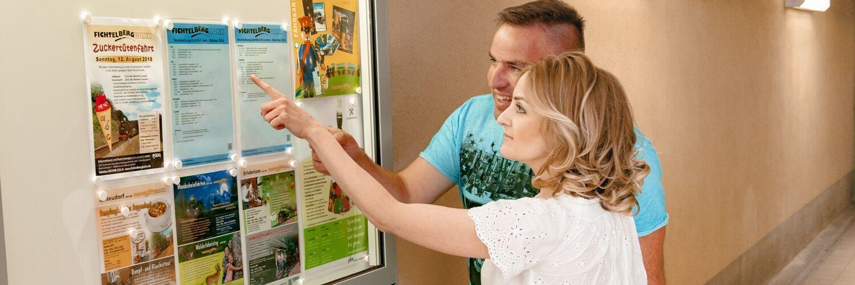 Paar schaut sich Informationstafel an