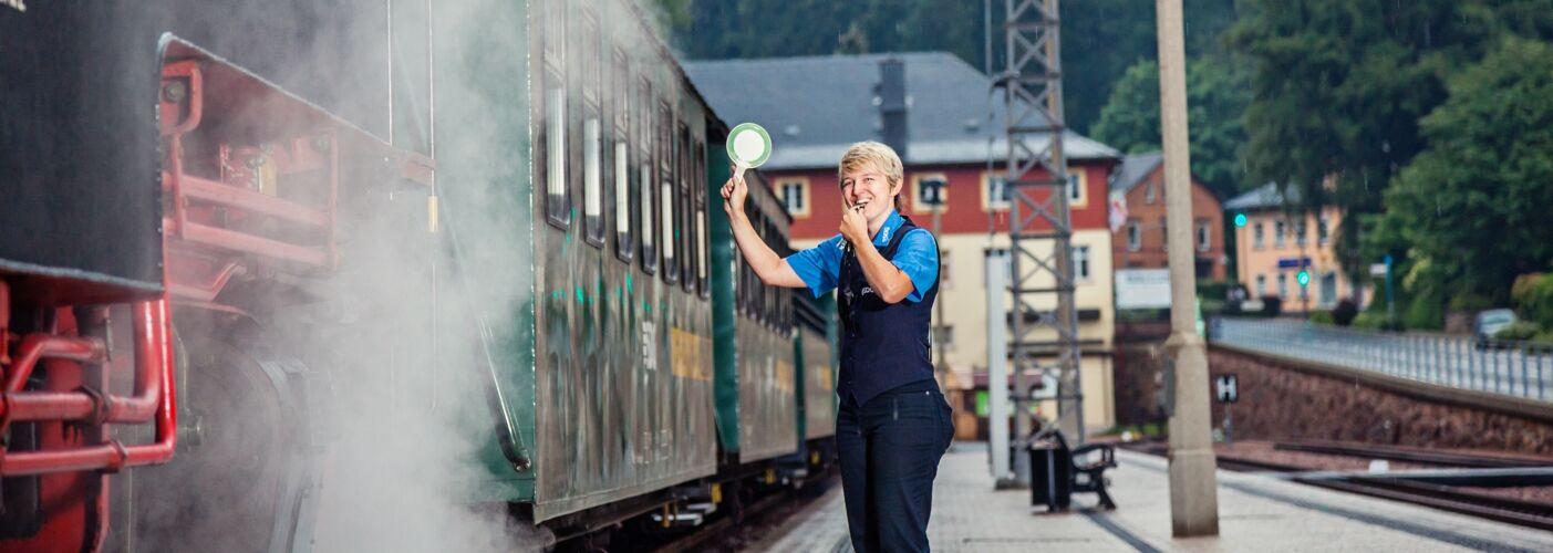 Freundliche Zugbegleiterin gibt Abfahrt