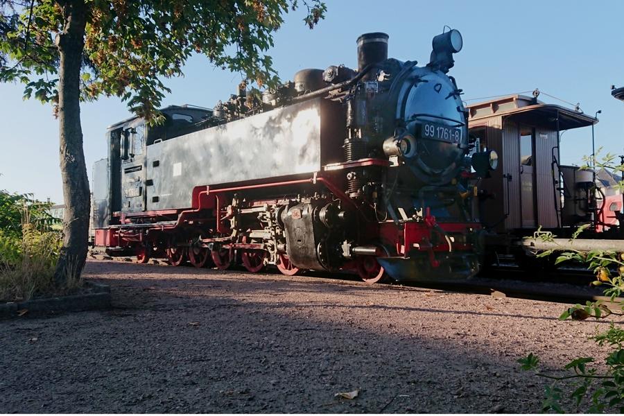 Dampflokomotve steht vor Eisenbahnwagen