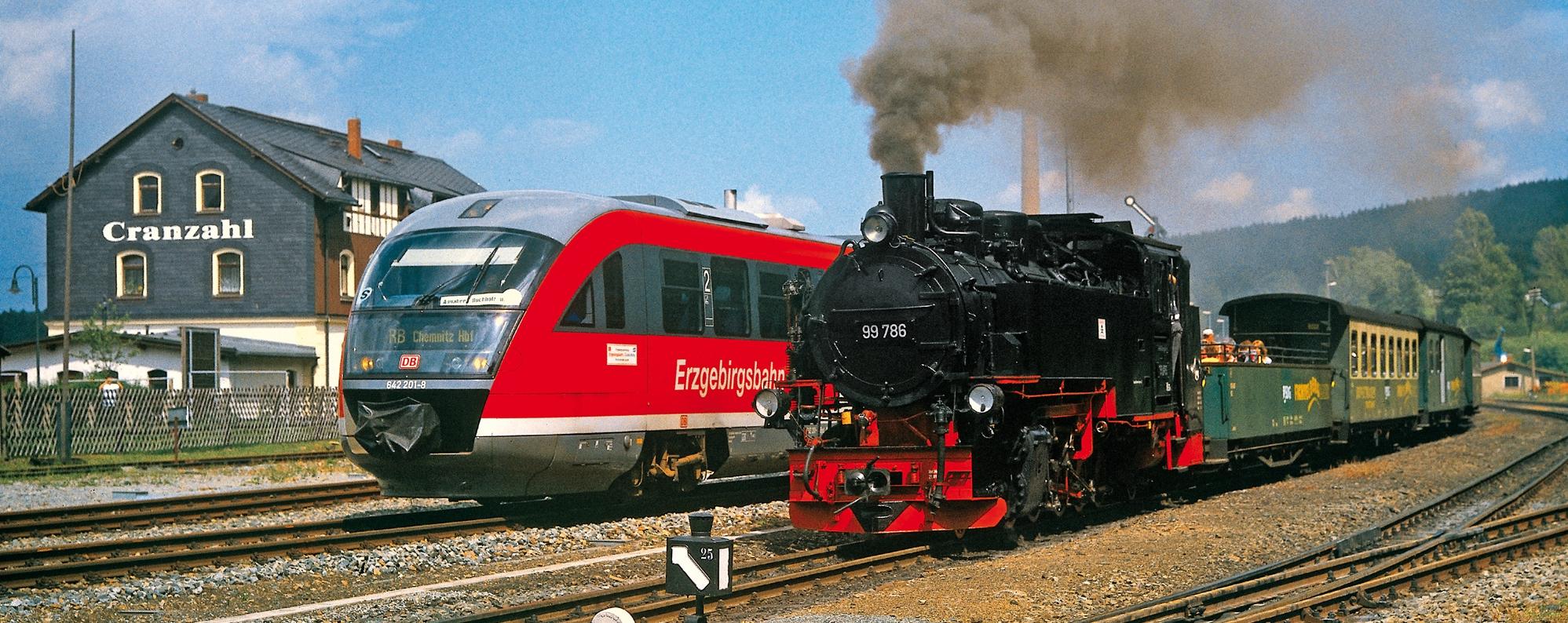 Triebwagen der Erzgebirgsbahn steht neben der Dampflok der Fichtelbergbahn